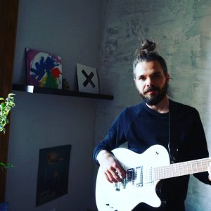 Pavel Trencsík musicuan artis and songwriter on the picture with guitar at home studio, working.